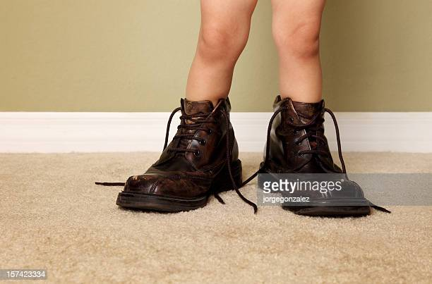 A young boy who decided to try on his father's shoes