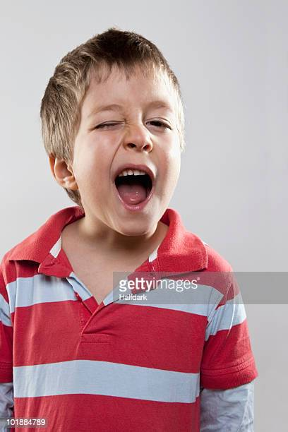 A young boy winking mischievously, studio shot