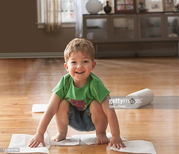 Young boy wiping floor with paper towels