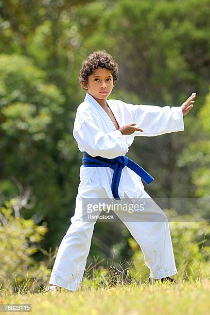Young boy with a black belt practices tae kwan do in the grass outside.