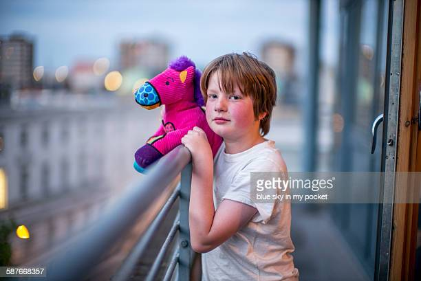 A young boy with a pink toy horse