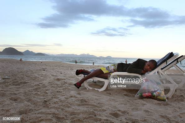 A young boy with a plastic bag full of cans to recycle rests on a beach chair on Copacabana beach in Rio de Janeiro Brazil July 05 2010 Photo by Lisa...