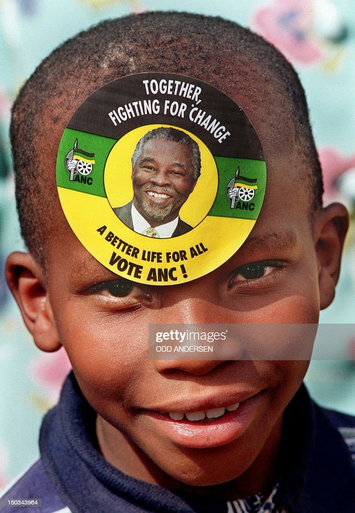 A young boy with a sticker of South African deputy President and President of the African National Congress Thabo Mbeki pasted on his forehead awaits...