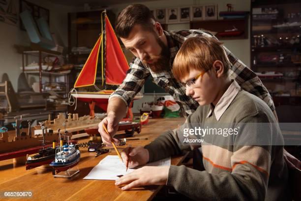 Kleiner Junge mit einem Lehrer zeichnet einen Plan des Schiffes