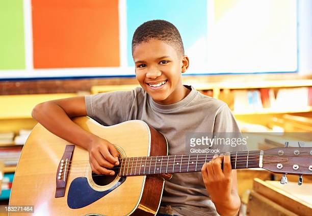 Young boy with acoustic guitar in classroom