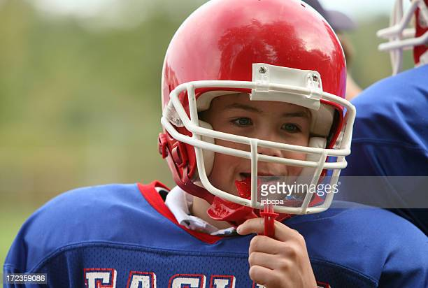 A young boy with an American Football uniform