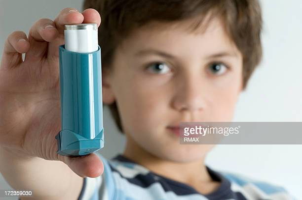 A young boy with asthma holding an inhaler