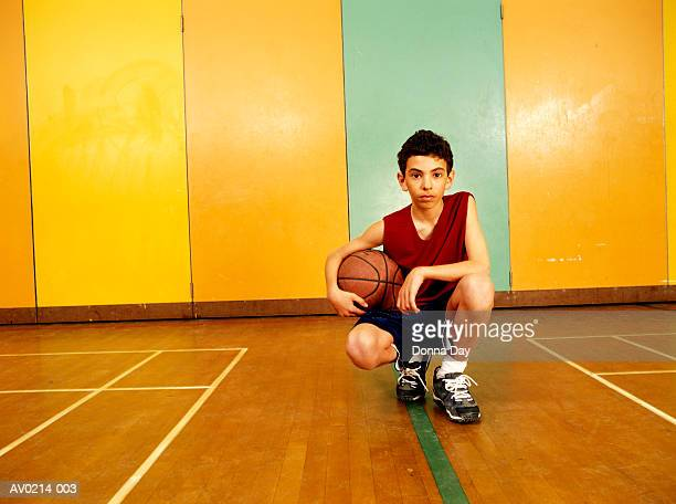 Young boy (12-14) with basketball, gym