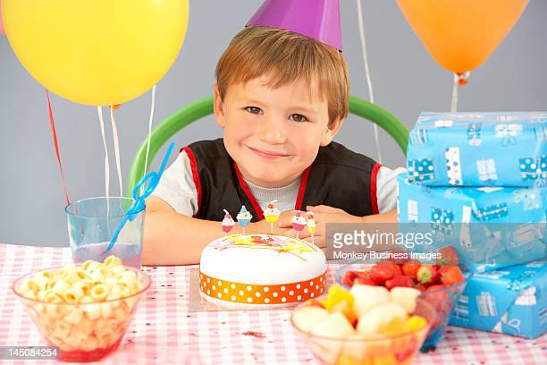 Young boy with birthday cake and gifts at party