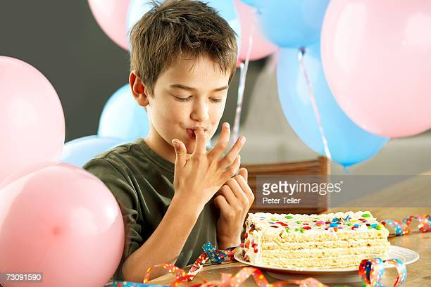 Young boy (10-11 years) with birthday cake, licking fingers