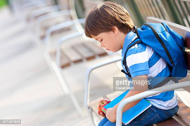 Young boy with blue backpack looking sad