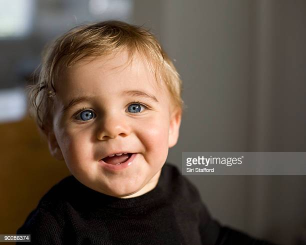Young boy with blue eyes smiling at camera
