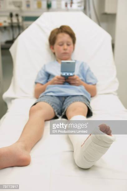 Young boy with broken leg in hospital bed playing video game