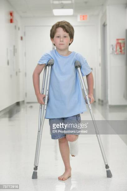 Young boy with broken leg walking on crutches