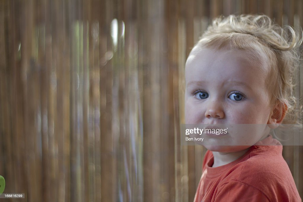 Young boy with curly hair looking at camera : Stock Photo