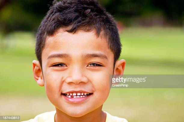 Young boy with dark hair and a missing tooth