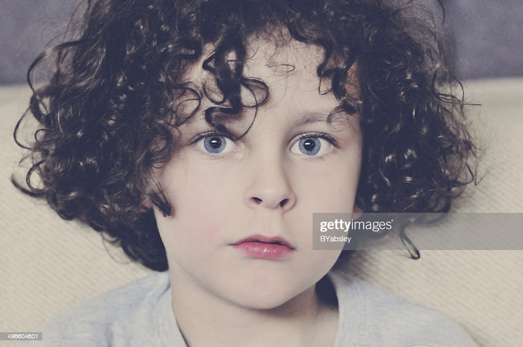 young boy with dark hair and blue eyes stock photo getty