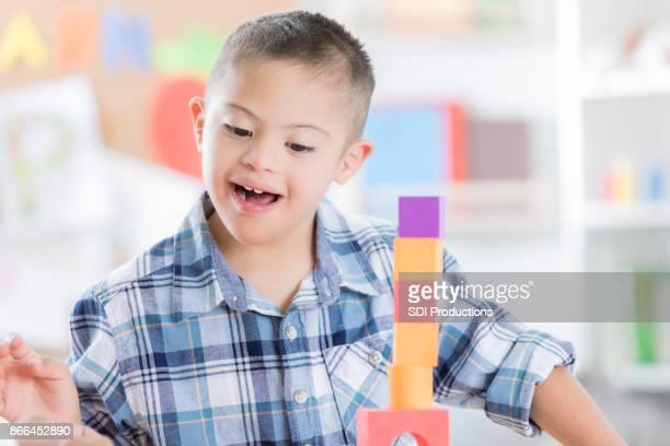 Junge mit Down-Syndrom baut einen Turm mit Blöcken