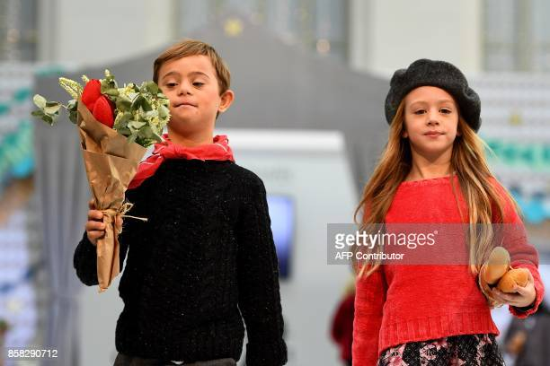 A young boy with Down Syndrome presents a creation on the catwalk during 'The Petite Fashion Week' in Madrid on October 6 2017 Some of the models at...