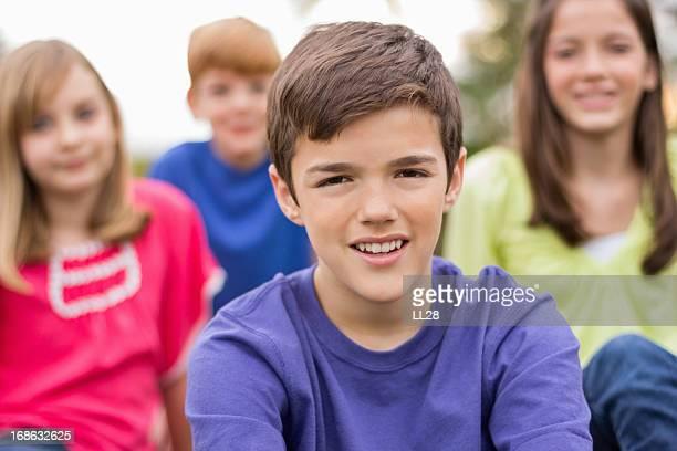 Jeune garçon avec des amis en arrière-plan
