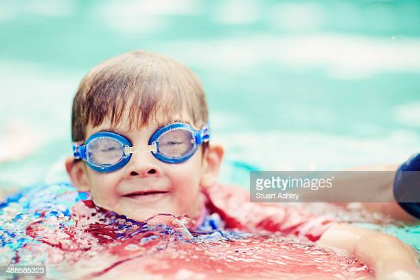 Young boy with goggles swimming in pool