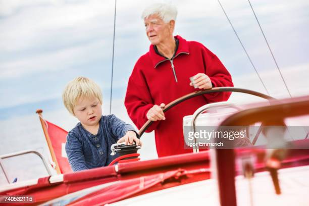 Young boy with great grandfather on sailing boat, Geneva, Switzerland, Europe