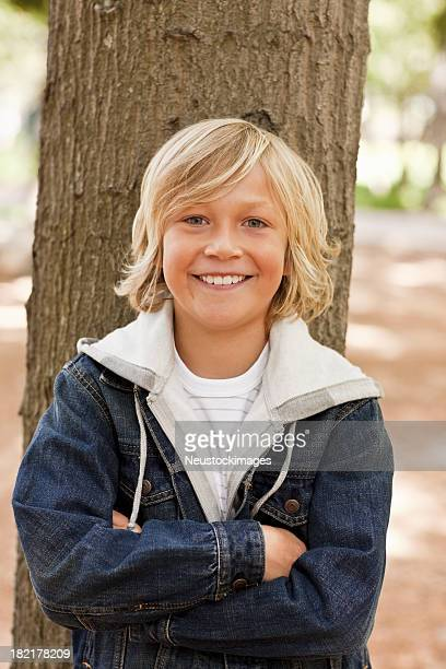 Young boy with hands folded at the park