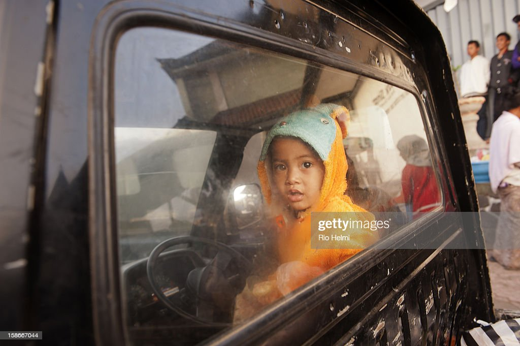 MARKET, KINTAMANI, BALI, INDONESIA - : A young boy with his father in their pick-up truck at sunrise in the markets of Kintamani,.