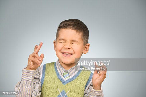 Young boy with his fingers crossed