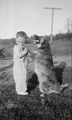 Young boy with his pet dog placing its front paws on the boys shoulders whilst standing on country roadside America circa 1950