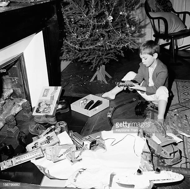 A young boy with his toys on christmas morning opens his presents close to the christmas tree on December 25 1963 in France