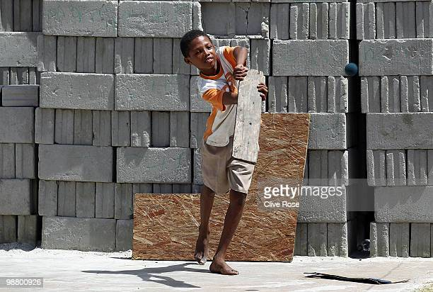 A young boy with hits a shot with his makeshift cricket bat and stumps on the sidelines during a street cricket match on May 2 2010 in Georgetown...