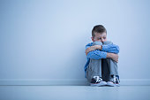 Young boy with hypersensitivity sitting alone on the floor against the wall with copy space