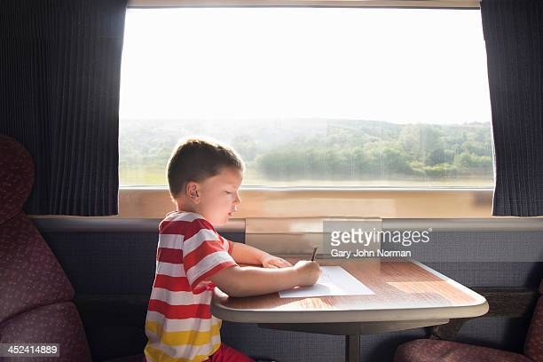 Young boy with pencil and paper on train