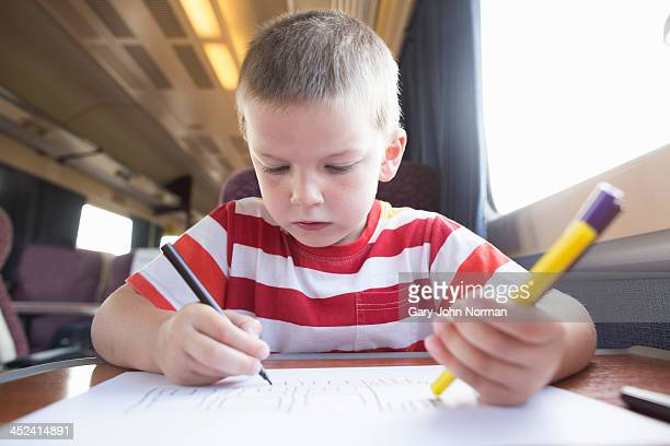 Young boy with pencil, pen and paper on train