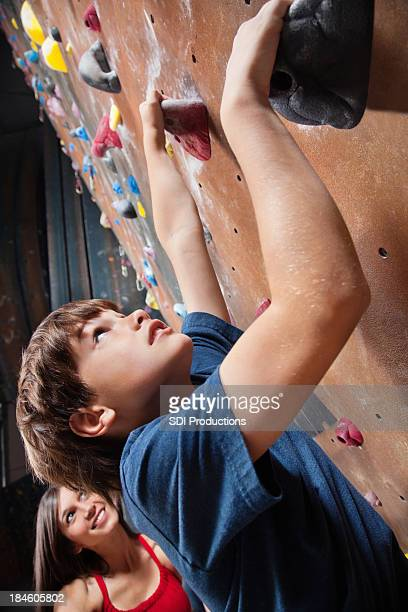Young boy with rock climbing instructor looking up wall
