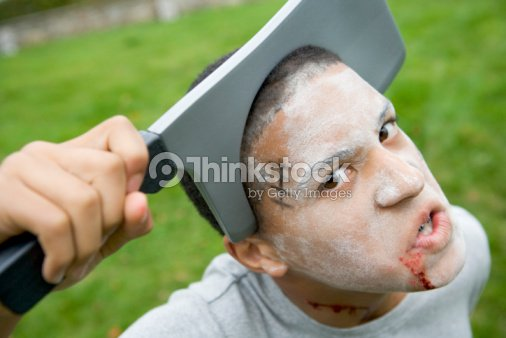 Young Boy With Scary Halloween Make Up And Plastic Knife Through ...