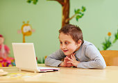 young boy with special needs watching media through the laptop