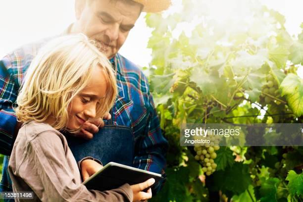 Jeune garçon avec tablette et grand-père dans les vignobles