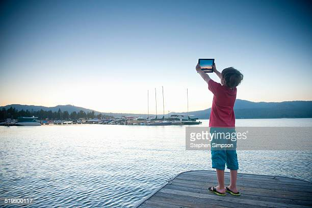 young boy with tablet on a dock at sunset