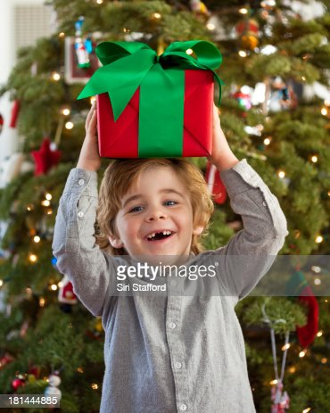 Young boy with two missing teeth holding present