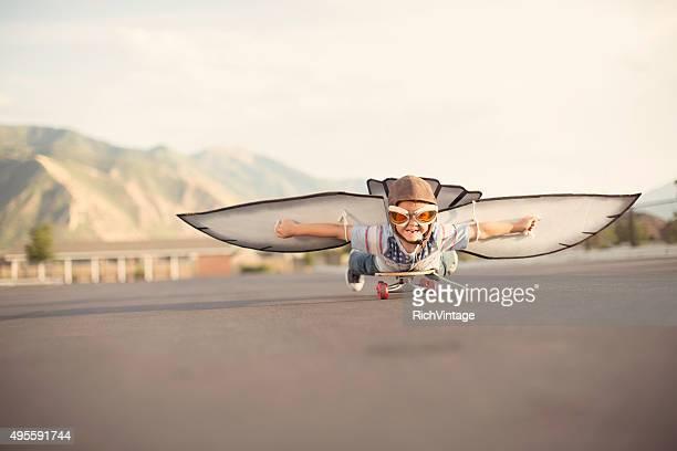 Jeune garçon avec des ailes mouches sur Skateboard