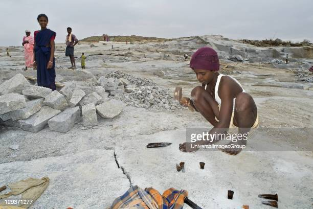 Young boy worker in granite quarry preparing rock slab for splitting Nandi hills Kolar distict Karnataka India