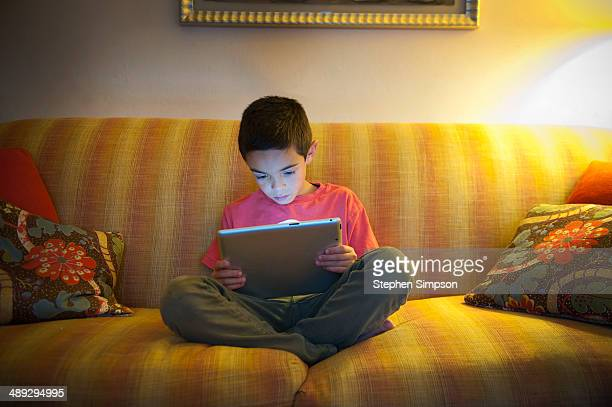 young boy working/playing on his tablet computer