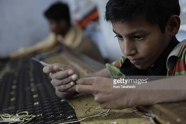 A young boy works in a textile factory November 18 2009 in Jaipur India Young boys mostly from rural area in Uttar Pradesh were bought off for 5000...
