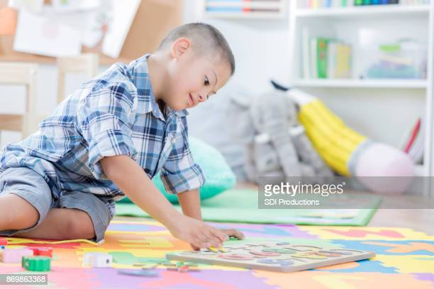 Young boy works on puzzle in preschool classroom