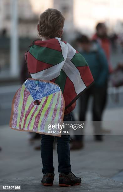 A young boy wrapped in a Basque flag and carrying a draw of a Catalan flag take part in a demonstration in support of Catalan independence in Bayonne...
