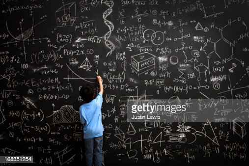 Young boy writes math equations on chalkboard : Stock Photo
