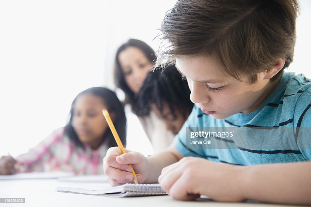 Young boy writing in notebook at school : Stock Photo
