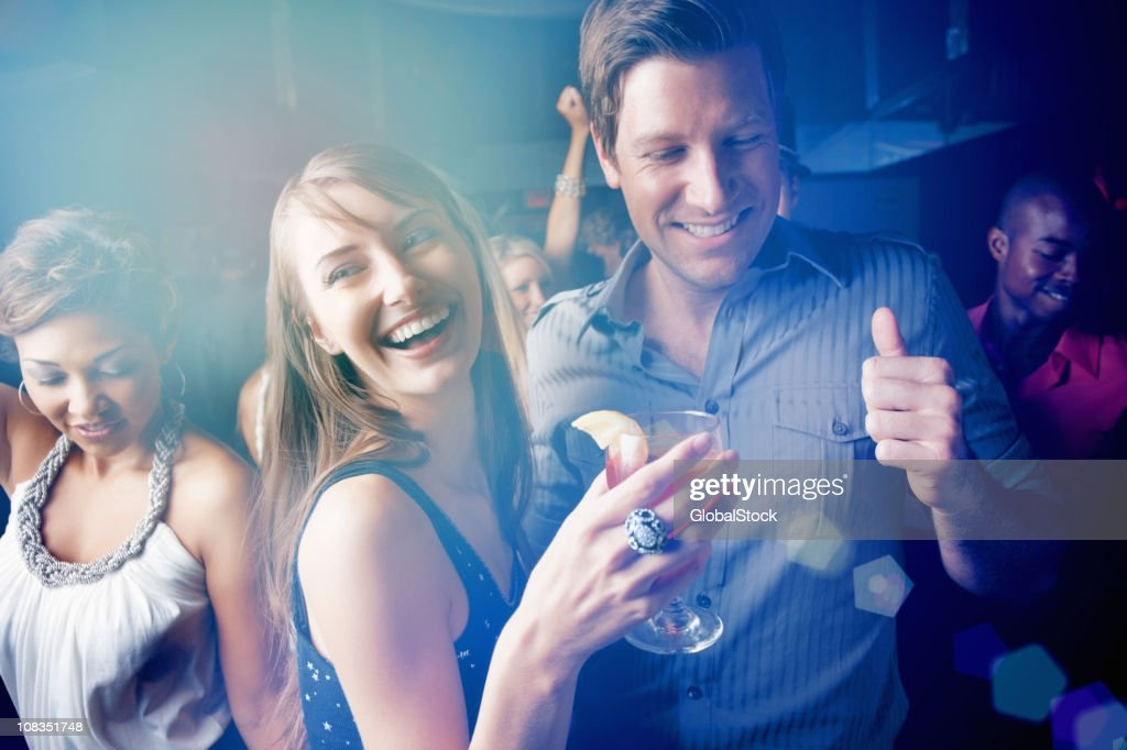 Young boys and girls dancing while enjoying at pub : Stock Photo